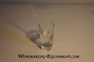 A home made hydrometer floating in a glass of water.